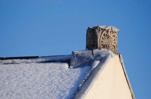 Part of roof with chimney covered in snow with clear blue sky