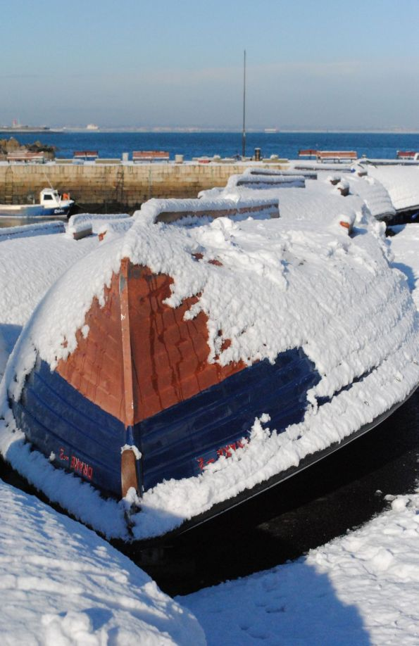 Boat lying up-side-down beside Bulloch Harbour covered with snow.